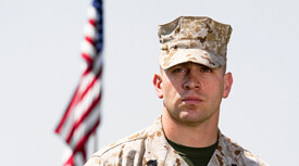 soldier standing in front of an American flag