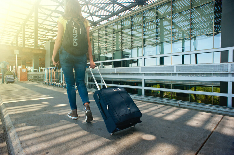 woman rolling suitcase in airport