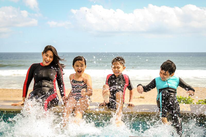 mom and kids splashing at the beach